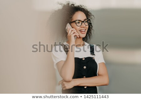 Smiling young curly woman with gentle smile, talks on mobile phone, has friendly conversation, wears Stock photo © vkstudio