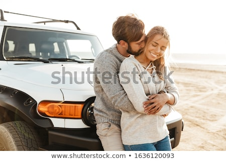 Loving couple outdoors at beach near car hugging. Stock photo © deandrobot