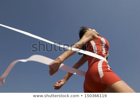 Woman running to cross finish line in competition Stock photo © jossdiim