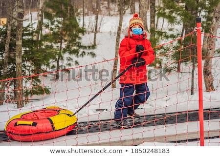Boy with tubing rises on a travelator to the mountain. Child having fun on snow tube. Boy is riding  Stock photo © galitskaya