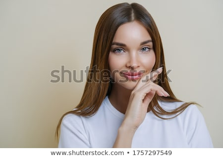 Natural beauty and women concept. Close up shot of pretty charming young woman touches cheeks gently Stock photo © vkstudio