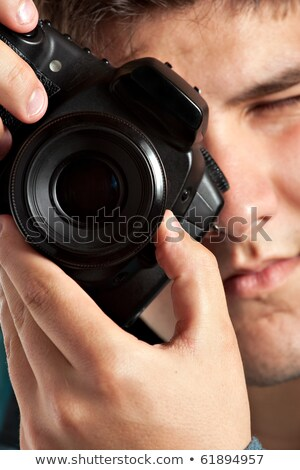 young teenage photographer taking a photo with his dslr camera stock photo © cozyta