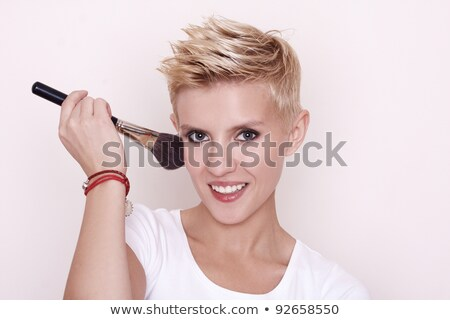 Portrait of attractive young adult woman applying blusher Stock photo © caimacanul