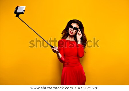 Woman with sunglasses in mouth while wearing red dress Stock photo © wavebreak_media