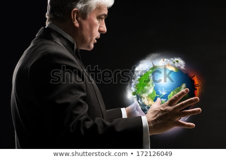 Senior business man holding planet in his arms and controlling i Stock photo © HASLOO