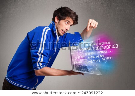 Casual man holding laptop with exploding data and numbers Stock photo © ra2studio