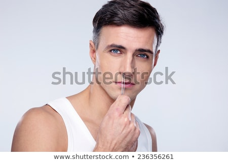 Man pucking nose hair with tweezers over gray background Stock photo © deandrobot