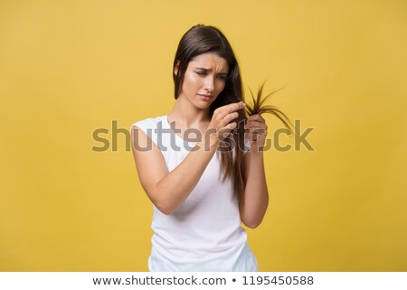 Young woman holding damaged long hair the hand and looking at split ends, isolated on white