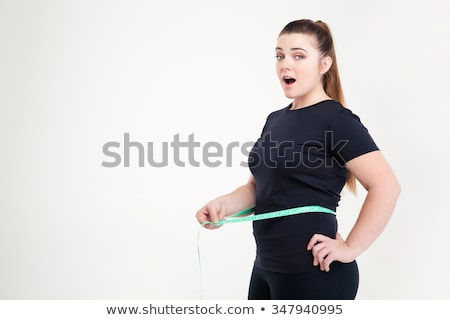 Stock fotó: Fat Woman Measuring Her Waist And Looking At Camera
