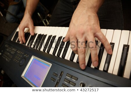 Hands of keyboard player on keys of synthesizer. focus on big finger of left hand Stock photo © Paha_L