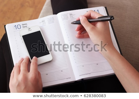 Hand writing mobile phone number in business agenda Stock photo © stevanovicigor