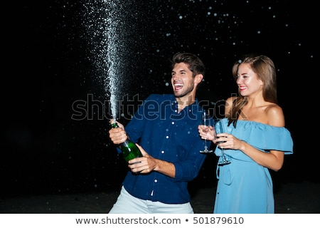 couple opening bottle of champagne on the beach at night stock photo © deandrobot