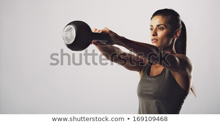 young beauty fitness woman doing exercise with dumbbells in studio stock photo © deandrobot