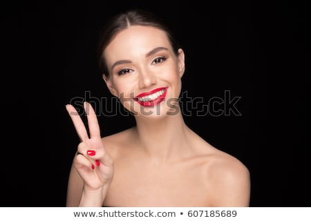 Beautiful woman with red lips showing peace gesture. Stock photo © deandrobot