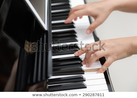 Young woman playing piano side view Stock photo © IS2