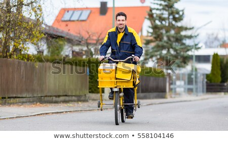Postman riding his cargo bike carrying out mail in neighborhood Stock photo © Kzenon