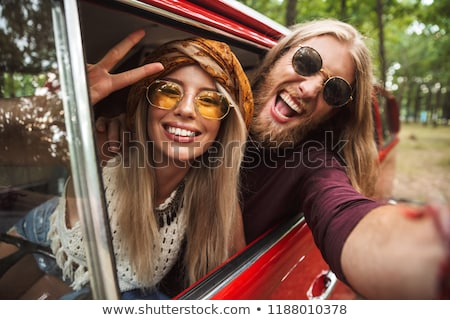 Photo of european hippie couple smiling, and showing peace sign  Stock photo © deandrobot