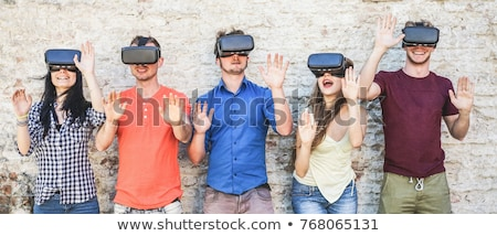 smiling man in virtual reality headset outdoors stock photo © dolgachov