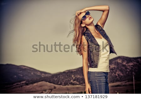Beautiful young woman posing on a road over picturesque landscape. stock photo © galitskaya