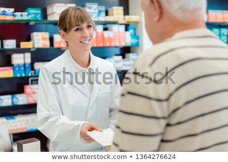 Pharmacist taking prescription slip from senior man ストックフォト © Kzenon