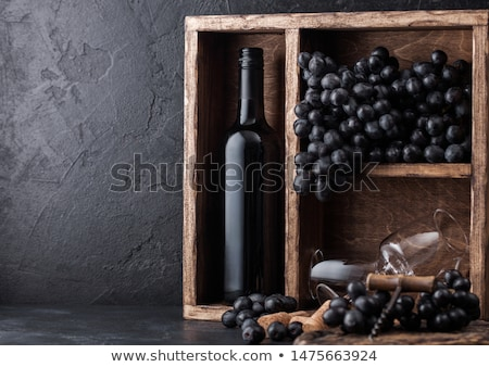 Stok fotoğraf: Luxury Bottle Of Red Wine And Empty Glasses With Dark Grapes With Corks And Corkscrew Inside Vintage