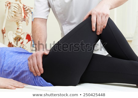 Male Osteopath Treating Female Patient With Hip Problem Stock photo © Lopolo