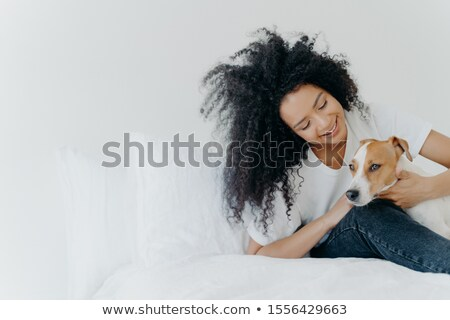 Indoor shot of lovely Afro American girl rests in bed after awakening with dog, enjoys time with pet Stock photo © vkstudio
