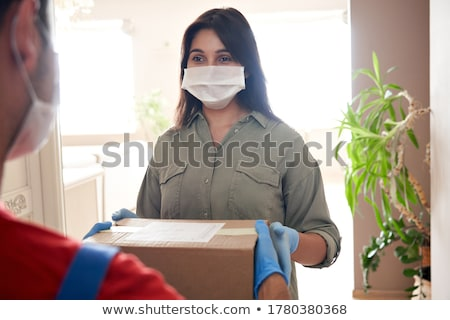 Volunteer in the protective medical mask and gloves delivery donation box at home Stock photo © Illia