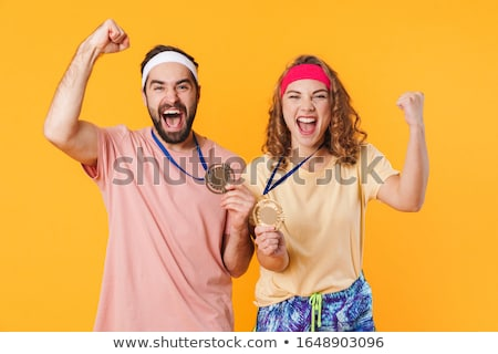 Portrait of athletic young couple celebrating victory with award Stock photo © deandrobot