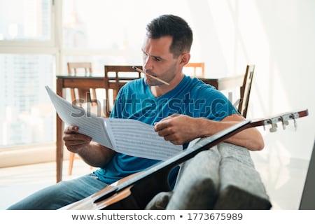 Volwassen man lezing akoestische gitaar bladmuziek appartement Stockfoto © diego_cervo