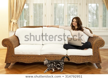 Portrait of a young woman sitting in front of her laptop on sofa Stock photo © HASLOO