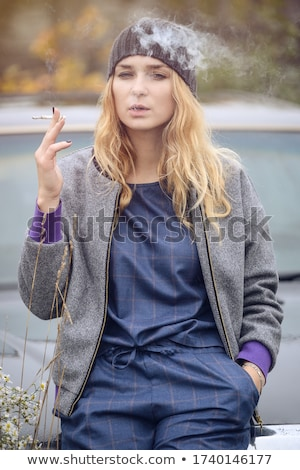 blonde smoking cigarette young fashion girl gray background stock photo © lunamarina