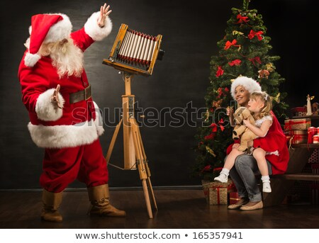 santa claus taking picture of cheerful woman with little girl by stock photo © hasloo