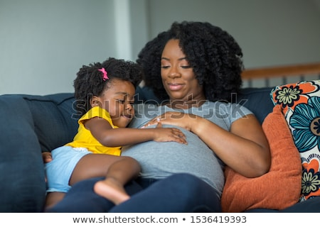 little girl and her pregnant mother with clothes for a baby Stock photo © phbcz