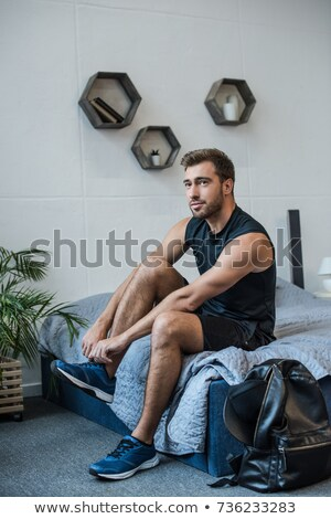 Handsome man lacing his shoes Stock photo © HASLOO