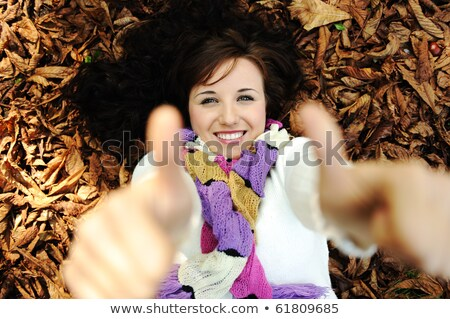 Young beauty girl laying on autumn ground and leaves with thumbs up Stock photo © zurijeta