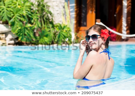 Woman with red bikini and flower in hair in infinity Pool  Stock photo © Kzenon