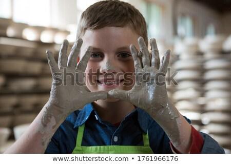 Boy showing clay hands in pottery shop Stock photo © wavebreak_media