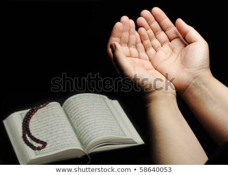 Hands up, islamic praying, Koran beside Stock photo © zurijeta