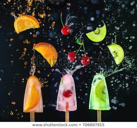 Orange ice cream lollty. Melting fruit ice cream with splashes a Stock photo © artjazz