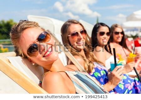 Four beautiful young women in swimwear drinking Stock photo © deandrobot
