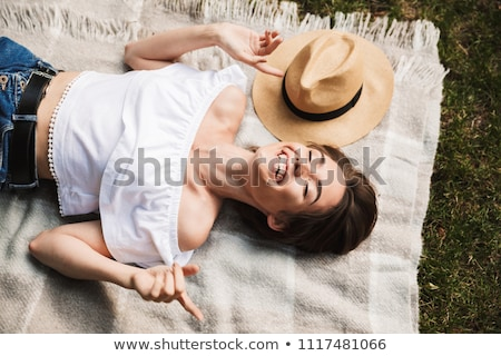 portrait of a smiling young girl laying on a grass stock photo © deandrobot