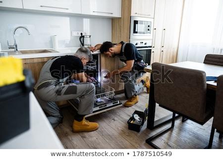 Szerelő megjavít mosogatógép fiatal elektromos fúró Stock fotó © AndreyPopov