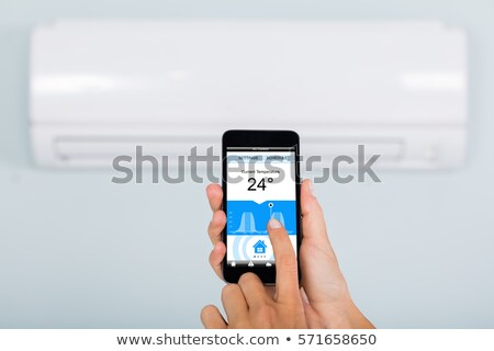 Woman Operating Thermostat Using Smartphone Stock photo © AndreyPopov