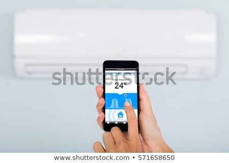 Femme thermostat smartphone main température Photo stock © AndreyPopov