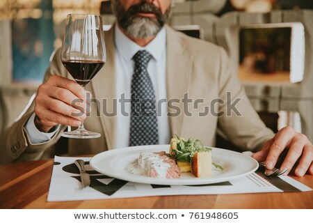 handsome bearded businessman having lunch and drinking red wine stock photo © boggy