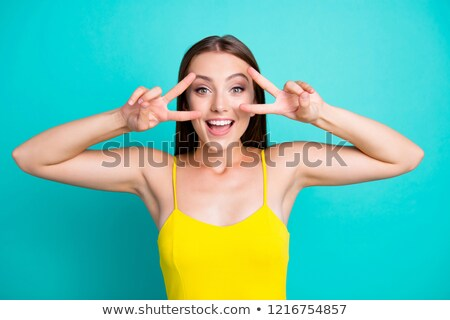 Excited young woman in green tanktop Stock photo © Kzenon