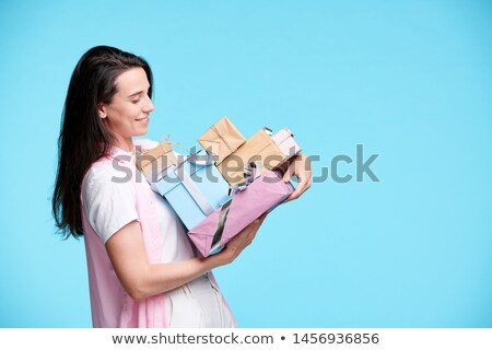 Happy young woman looking at pile of giftboxes in her hands Stock photo © pressmaster