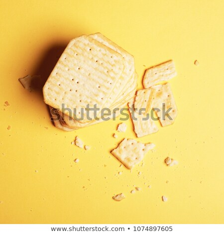 Minimalism. Flat lay. Top view. Unhealthy food. Salty crackers on a yellow background Stock photo © serdechny
