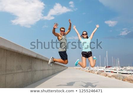 Boldog pár sportok ruházat ugrik móló Stock fotó © dolgachov